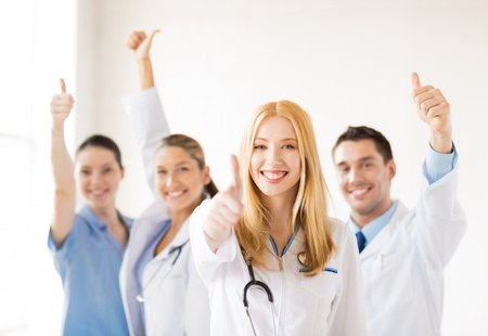 Photo pour attractive female doctor with group of doctors showing thumbs up - image libre de droit