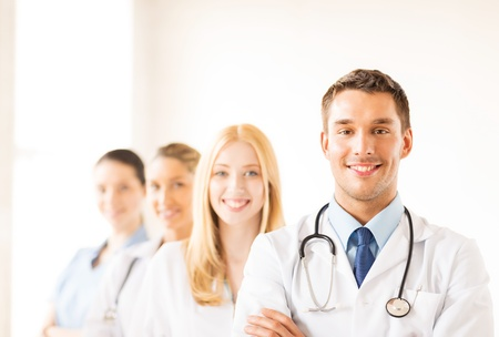 Photo pour attractive male doctor in front of medical group - image libre de droit