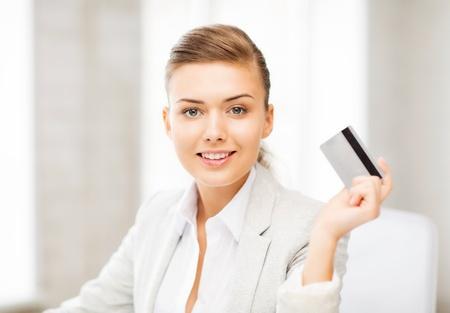 Photo pour bright picture of smiling businesswoman showing credit card - image libre de droit