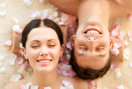 faces of couple in spa salon lying on the massage desksの写真素材
