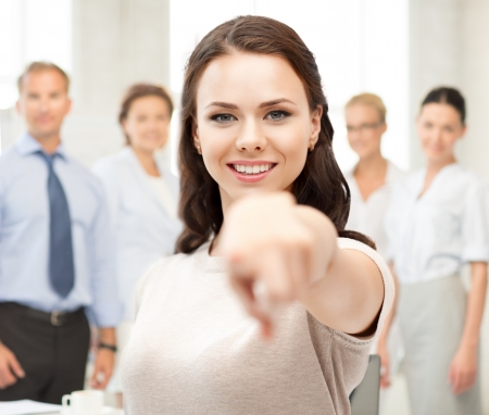 business concept - attractive young businesswoman pointing at you in office