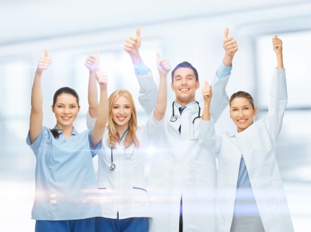 healthcare and medical - professional young team or group of doctors showing thumbs up