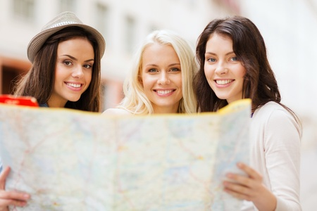 Photo pour holidays and tourism concept - beautiful girls looking into tourist map in the city - image libre de droit