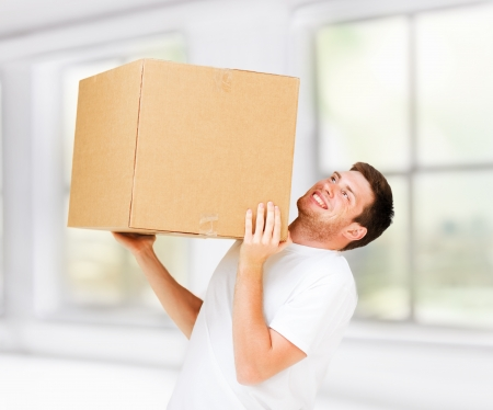new home and post delivery concept - man carrying carton heavy box