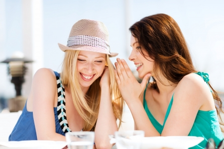 summer holidays and vacation - girls gossiping in cafe on the beach
