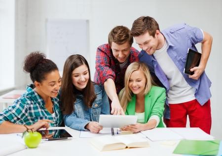 Foto de education concept - smiling students looking at tablet pc at school - Imagen libre de derechos