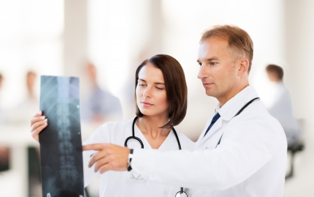 healthcare, medical and radiology concept - two doctors looking at x-ray
