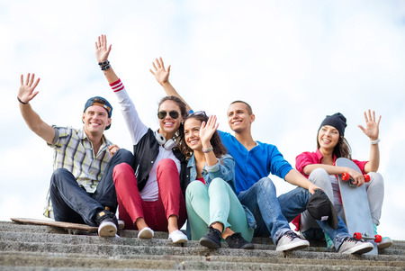 summer holidays and teenage concept - group of teenagers waving hands outside