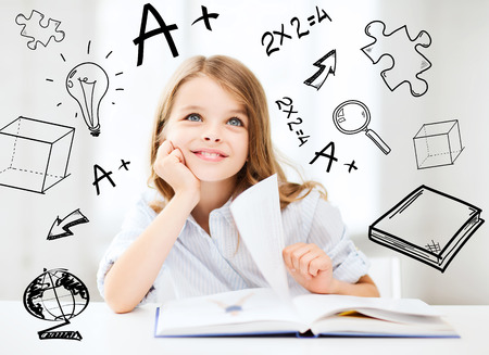 Foto de education and school concept - little student girl studying at school - Imagen libre de derechos