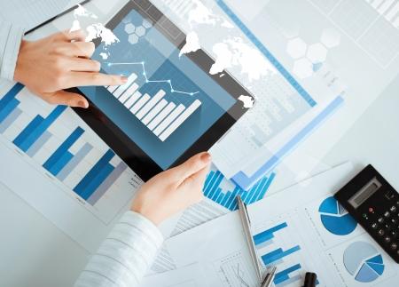 Foto de business, office, school and education concept - woman with tablet pc and chart papers - Imagen libre de derechos