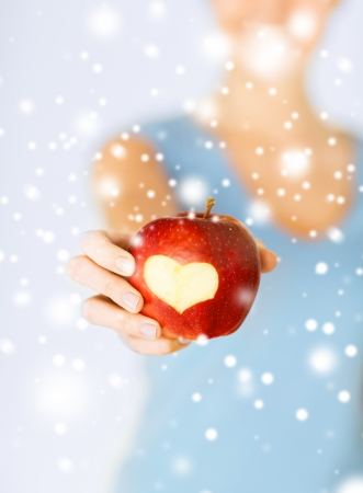 Foto de healthy food and lifestyle - woman hand holding red apple with heart shape - Imagen libre de derechos