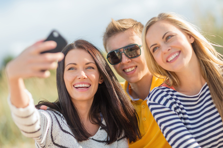 summer, holidays, vacation, happy people concept - group of friends taking photo picture with smartphone