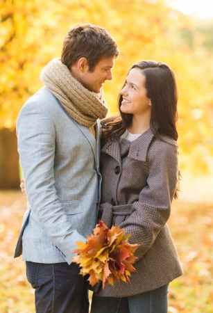 holidays, love, travel, tourism, relationship and dating concept - romantic couple kissing in the autumn parkの写真素材