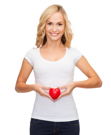 shirt design, health, charity, pregnancy, digestion, love concept - smiling woman in blank white shirt with small red heart