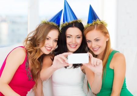 celebration, friends, bachelorette party, birthday concept - three smiling women in blue hats having fun with smartphone photo cameraの写真素材