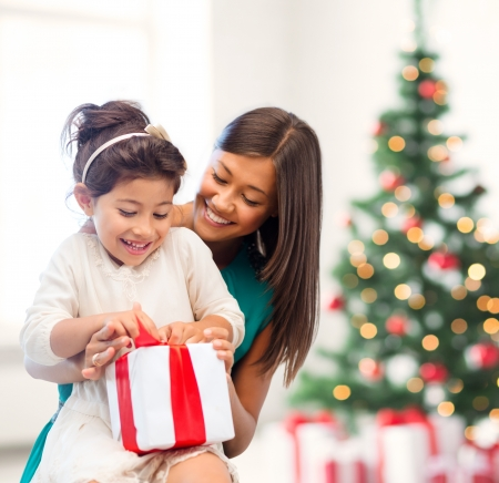 holidays, presents, christmas, x-mas, birthday concept - happy mother and child girl with gift boxの写真素材