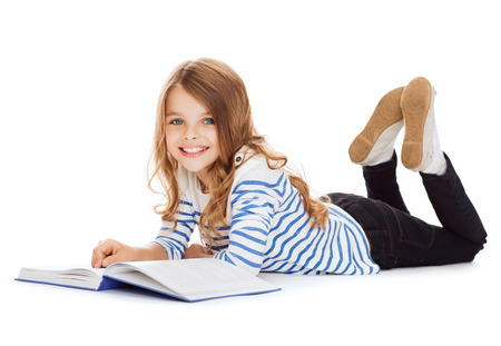 education and school concept - smiling little student girl with book lying on the floor