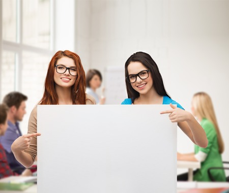 vision, health, advertisement and people concept - two smiling girls wearing eyeglasses pointing fingers to white blank board