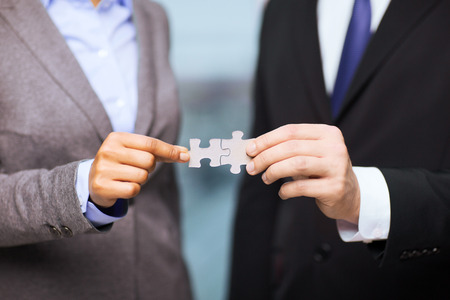 Photo pour business and office concept - businessman and businesswoman holding puzzle pieces in office - image libre de droit