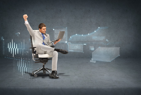 business, internet and technology concept - young businessman sitting in chair with laptop with virtual screensの写真素材
