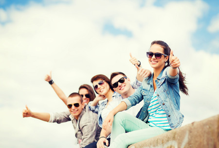 summer holidays and teenage concept - group of teenagers showing thumbs up