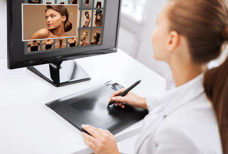 photography, office and magazine concept - female retoucher with drawing tablet and computer working at home or office