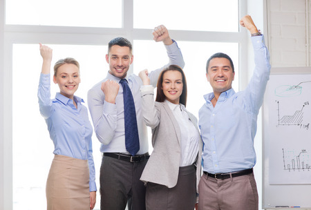 business, office, success and victory concept - happy business team celebrating victory in office