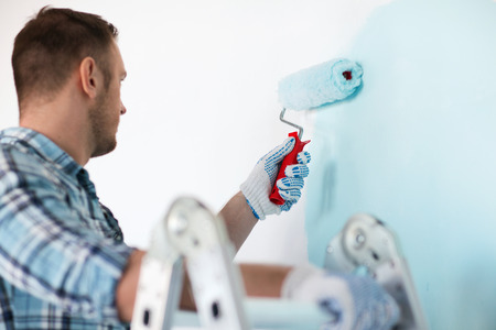 Photo for repair, building and home concept - close up of male in gloves holding painting roller - Royalty Free Image