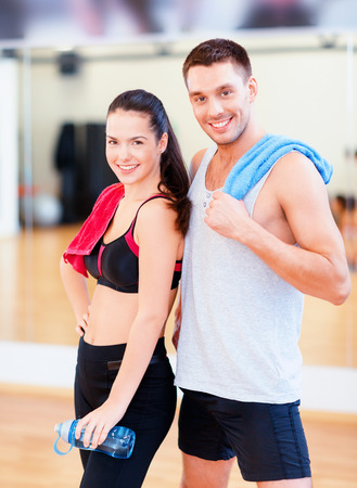 fitness, sport, training, gym and lifestyle concept - two smiling people in the gym