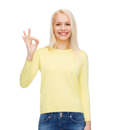 happiness, gesture and people concept - young businesswoman showing ok sign