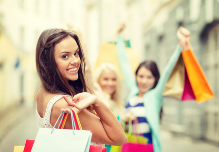 sale, shopping, tourism and happy people concept - beautiful woman with shopping bags in the ctiyの写真素材