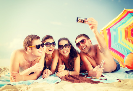 Photo pour summer, holidays, vacation, technology and happiness concept - group of smiling people in sunglasses taking picture with smartphone on beach - image libre de droit