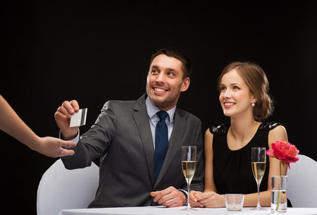 restaurant, couple and holiday concept - smiling couple paying for dinner with credit card at restaurant