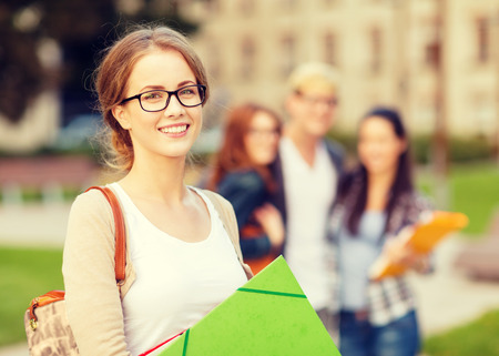 Foto de summer holidays, education, campus and teenage concept - smiling female student in black eyeglasses with folders and group in the back - Imagen libre de derechos