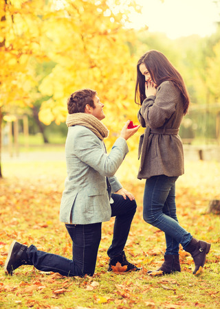 Photo for holidays, love, couple, relationship and dating concept - kneeled man proposing to a woman in the autumn park - Royalty Free Image
