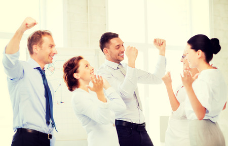 picture of happy business team celebrating victory in officeの写真素材