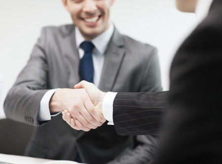 Photo pour businesss and office concept - two businessmen shaking hands in office - image libre de droit