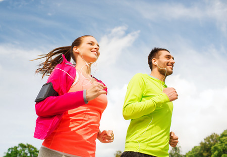 fitness, sport, friendship and lifestyle concept - smiling couple with earphones running outdoorsの写真素材