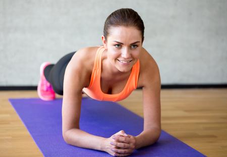 Foto de fitness, sport, training and lifestyle concept - smiling woman doing exercises on mat in gym - Imagen libre de derechos