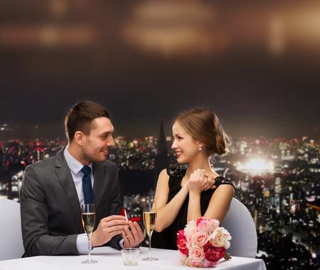 Foto de restaurant, couple and holiday concept - smiling man proposing to his girlfriend at restaurant - Imagen libre de derechos