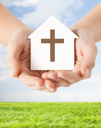 religion, christianity and charity concept - close up of woman hands holding paper house with christian cross symbol over blue sky with grass background