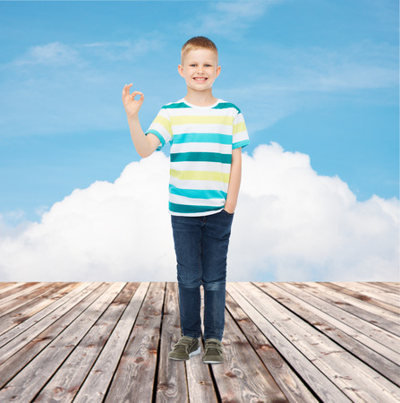 happiness, childhood and people concept - smiling little boy in casual clothes making ok gesture over blue sky and wooden floor background