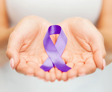 healthcare and social problems concept - womans hands holding purple domestic violence awareness ribbon