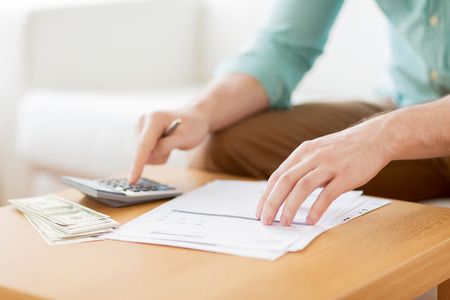 Photo pour savings, finances, economy and home concept - close up of man with calculator counting money and making notes at home - image libre de droit