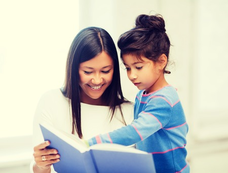 family, children, education, school and happy people concept - mother and daughter with bookの写真素材