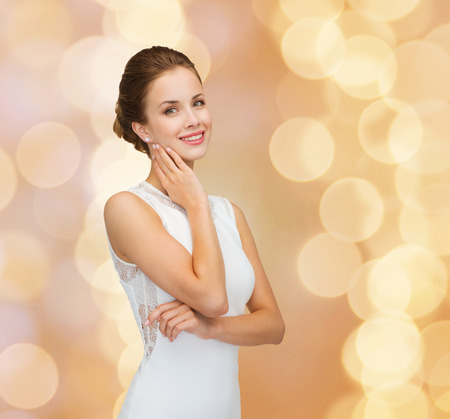 holidays, celebration, wedding and people concept - smiling woman in white dress wearing diamond ring over golden lights