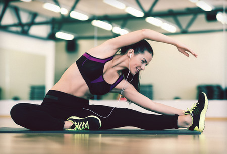 Foto de fitness, sport, training, gym and lifestyle concept - stretching young woman with earphones in the gym - Imagen libre de derechos