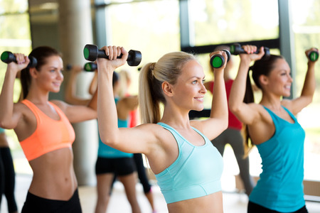 Foto de fitness, sport, training and lifestyle concept - group of women with dumbbells in gym - Imagen libre de derechos