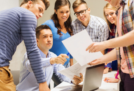 Photo for education, high school, technology and people concept - group of smiling students and teacher with papers, laptop computer in classroom - Royalty Free Image
