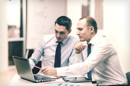 two businessmen with laptop, tablet pc computer and papers having discussion in office